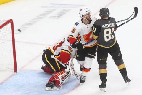 Golden Knights defenseman Deryk Engelland, not pictured, sends the puck past Calgary Flames goaltender David Rittich (33) and defenseman Noah Hanifin (55) as Golden Knights center Jonathan Marches ...