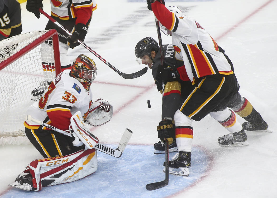 Golden Knights left wing Max Pacioretty tries to get the puck in between Calgary Flames goaltender David Rittich (33) and defenseman Rasmus Andersson during the third period of an NHL hockey game ...