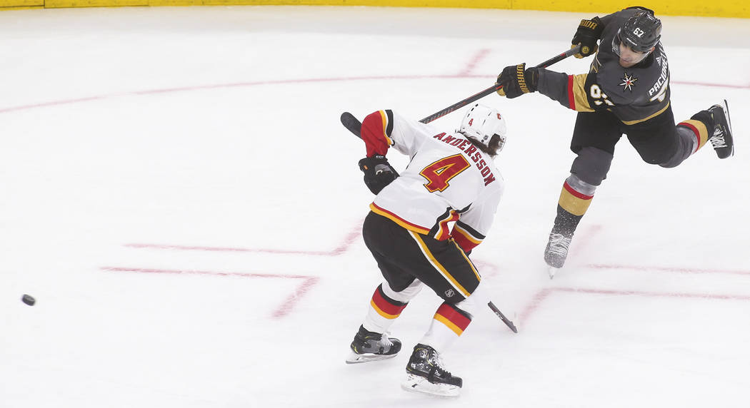 Golden Knights left wing Max Pacioretty (67) shoots the puck past Calgary Flames defenseman Rasmus Andersson (4) during the third period of an NHL hockey game at T-Mobile Arena in Las Vegas on Wed ...