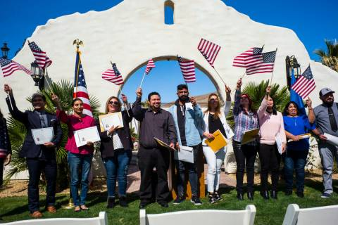 Attendees including Mandeep Kaur of Bakersfield, Calif., second from the left, and Raul Vargas, originally from Guatemala, the fourth from the left, pose for photographs while waving their flags a ...