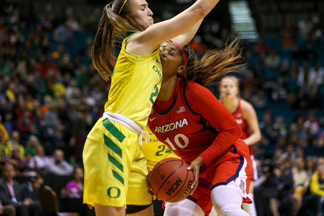 Arizona Wildcats forward Tee Tee Starks (10) falls into Oregon Ducks guard Sabrina Ionescu (20) during the first half of an NCAA college basketball game at the Pac-12 women's tournament at the MGM ...