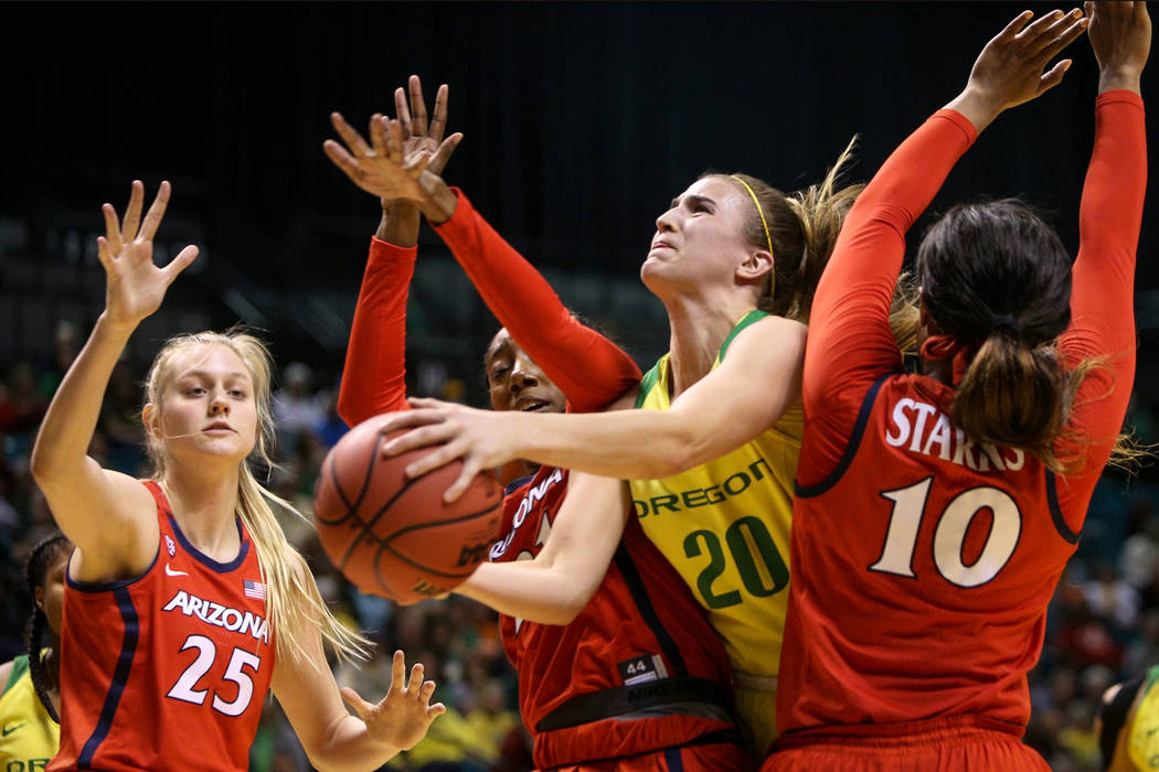 Oregon Ducks guard Sabrina Ionescu (20) pushes through Arizona Wildcats forward Destiny Graham (21) and Arizona Wildcats forward Tee Tee Starks (10) with the ball during the second half of an NCAA ...