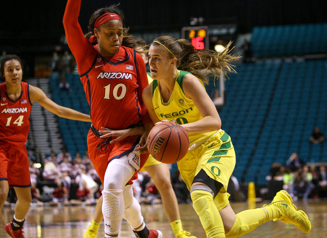Oregon Ducks guard Sabrina Ionescu (20) drives past Arizona Wildcats forward Tee Tee Starks (10) with the ball during the second half of an NCAA college basketball game at the Pac-12 women's tourn ...
