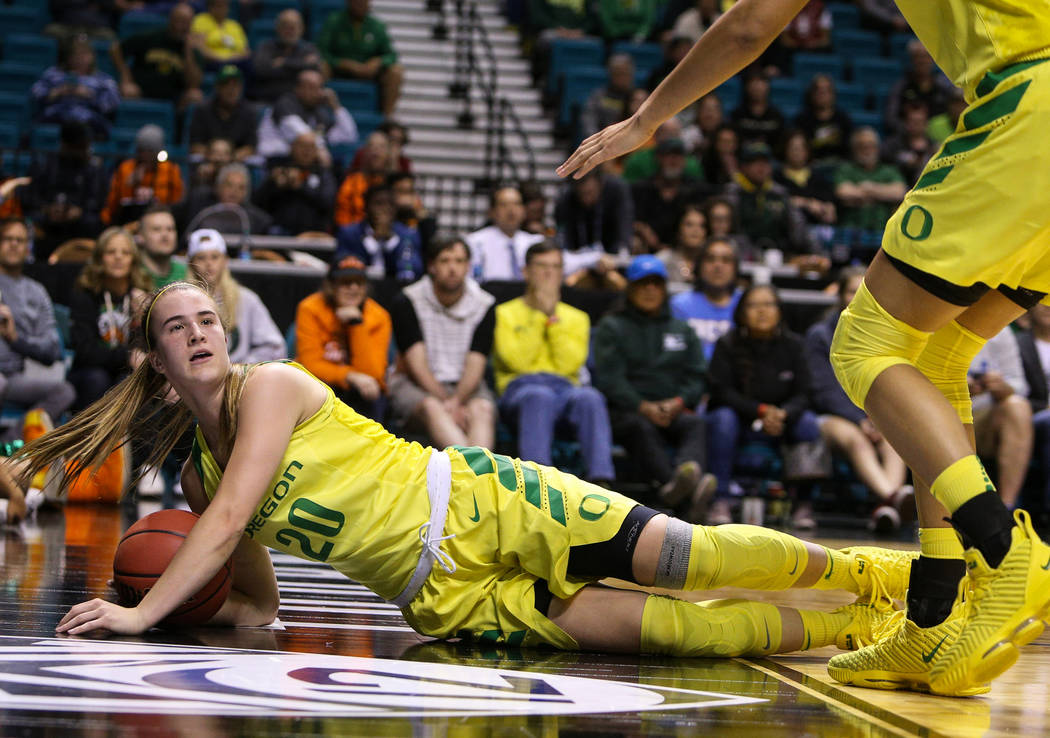 Oregon Ducks guard Sabrina Ionescu (20) falls down wit the ball during the second half of an NCAA college basketball game at the Pac-12 women's tournament at the MGM Grand Garden Arena in Las Vega ...
