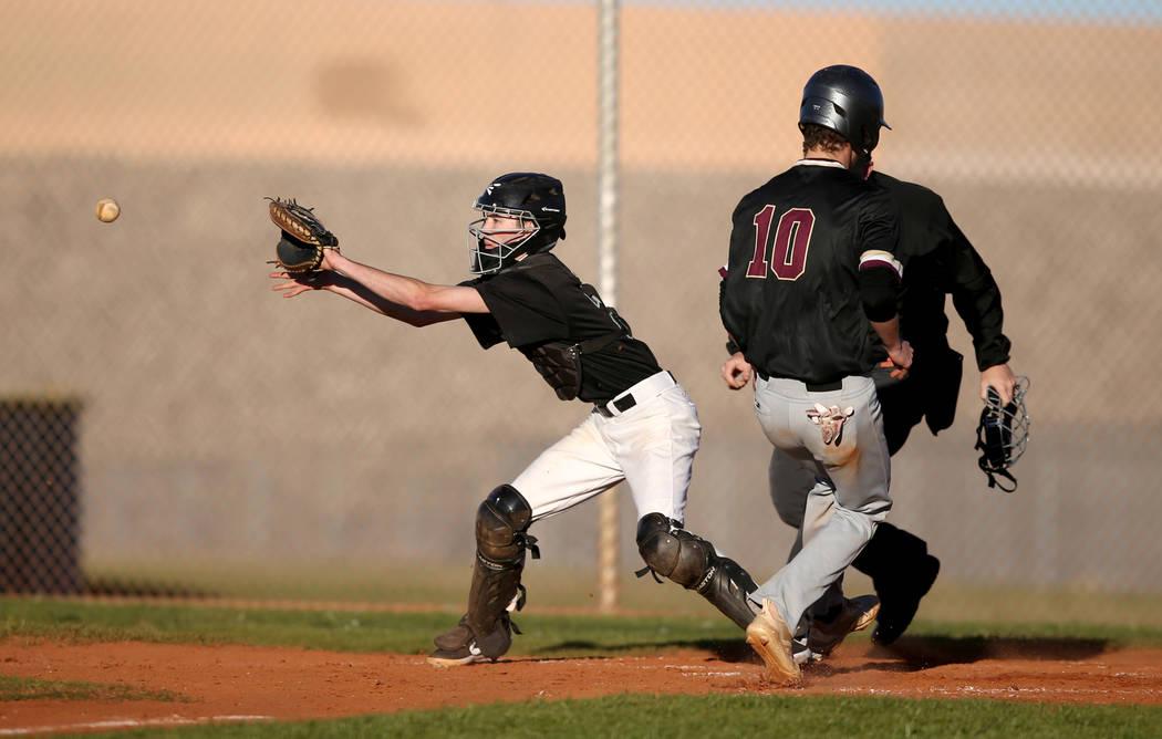 Faith Lutheran Michael Carroll (10) crosses home as Silverado catcher Seton Cifelli (21) fields the throw during a baseball game at Silverado High School in Las Vegas Friday, March 8, 2019. (K.M. ...