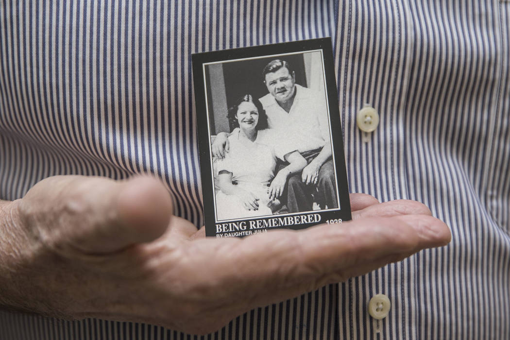 Tom Stevens, the grandson of Babe Ruth, holds a commemorative card showing his mother Julia Ruth Stevens, left, with her father Babe Ruth, on Thursday, Jan. 31, 2019, at Stevens' home, in the Las ...