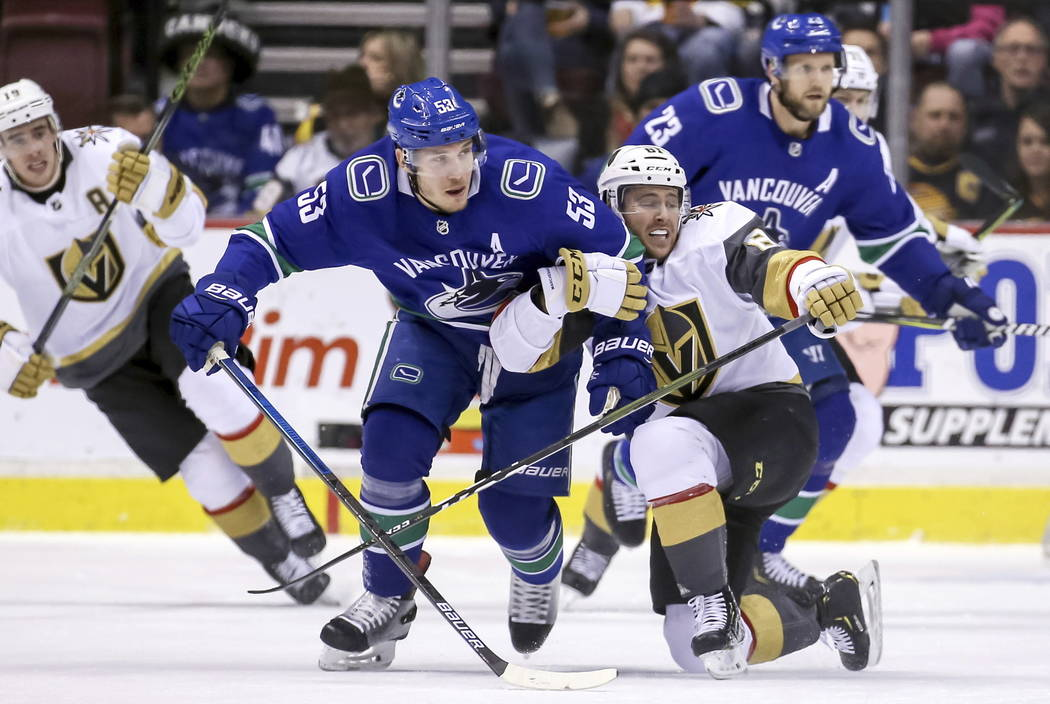 Vegas Golden Knights' Jonathan Marchessault (81) fights for the puck with Vancouver Canucks' Bo Horvat (53) during the first period of an NHL hockey game in Vancouver, British Columbia, Saturday, ...