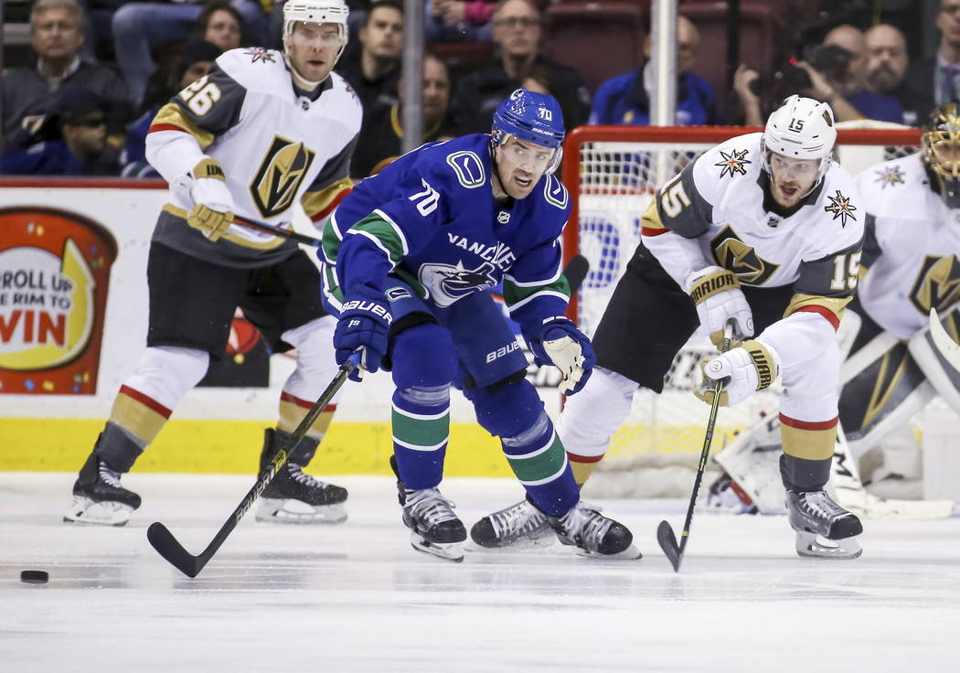 Vegas Golden Knights' Jon Merrill (15) fights for the puck against Vancouver Canucks' Tanner Pearson (70) during the second period of an NHL hockey game in Vancouver, British Columbia, Saturday, M ...