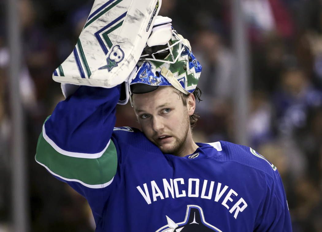Vancouver Canucks goaltender Thatcher Demko (35) adjusts his mask during the second period of an NHL hockey game against the Vegas Golden Knights in Vancouver, British Columbia, Saturday, March 9, ...