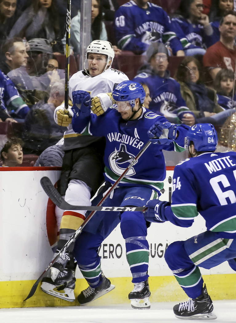 Vegas Golden Knights' Brayden McNabb (3) is checked by Vancouver Canucks' Jay Beagle (83) during the second period of an NHL hockey game in Vancouver, British Columbia, Saturday, March 9, 2019. (B ...