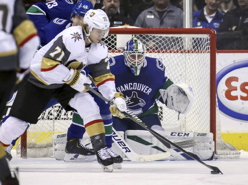 Vegas Golden Knights' William Karlsson (71) skates with the puck near Vancouver Canucks goaltender Jacob Markstrom (25) during the first period of an NHL hockey game in Vancouver, British Columbia ...