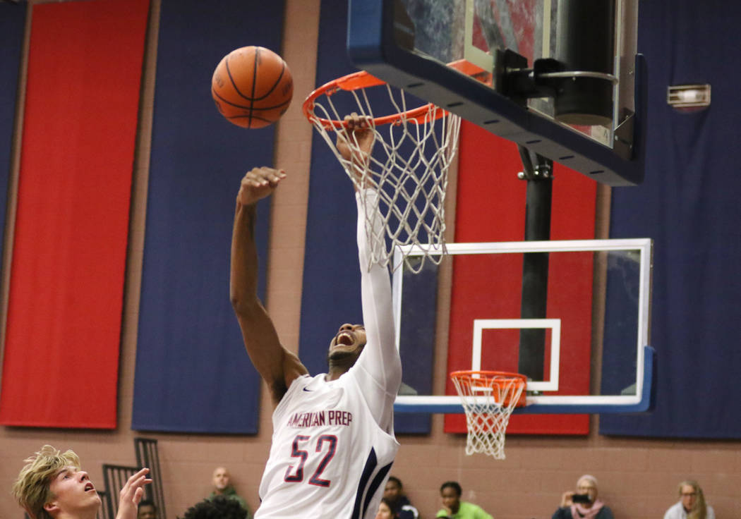 Darren Jones (52) grabs the rim as he tries to dunk the basketball during a game against SLAM Academy at American Preparatory Academy in Las Vegas, Thursday, Jan. 17, 2019. (Heidi Fang /Las Vegas ...