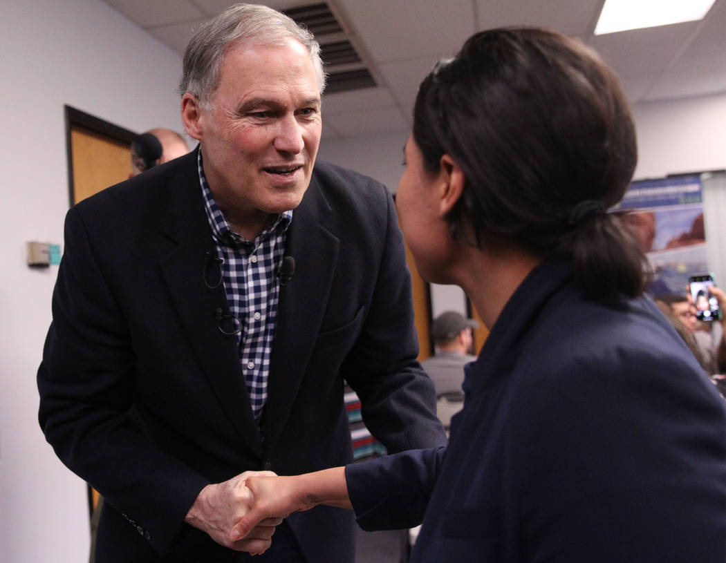 Washington Gov. Jay Inslee, left, a Democratic presidential candidate, shakes hands with Blanca Ortiz, organizer for the Nevada Conservation League, after speaking on climate change at the Nevada ...