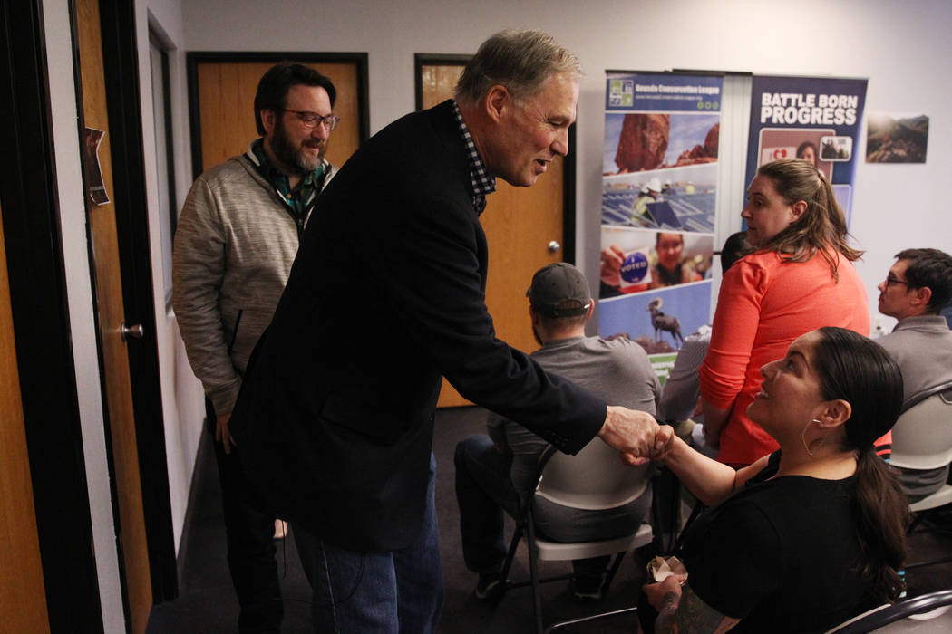 Washington Gov. Jay Inslee, left, a Democratic presidential candidate, shakes hands with Fawn Douglas, after speaking on climate change at the Nevada Conservation League offices in Las Vegas, Satu ...