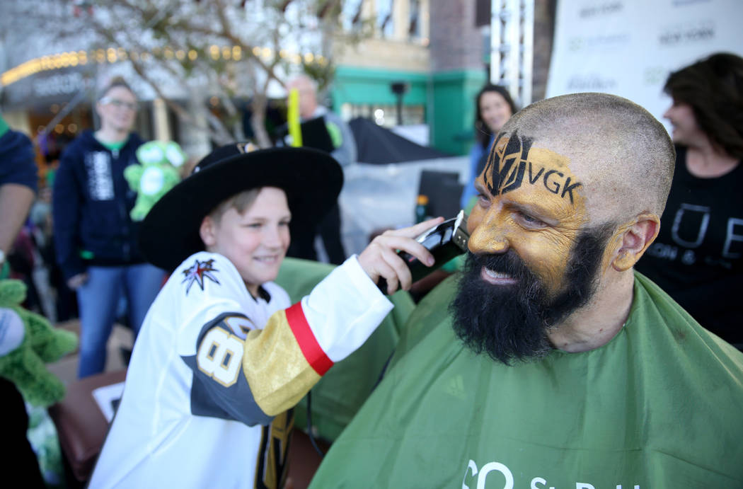 John McManus of Las Vegas gets his beard shaved by son Peter McManus, 11, during St. Baldrick's Foundation shave-a-thon on the Brooklyn Bridge at New York-New York in Las Vegas, Saturday, March 9, ...