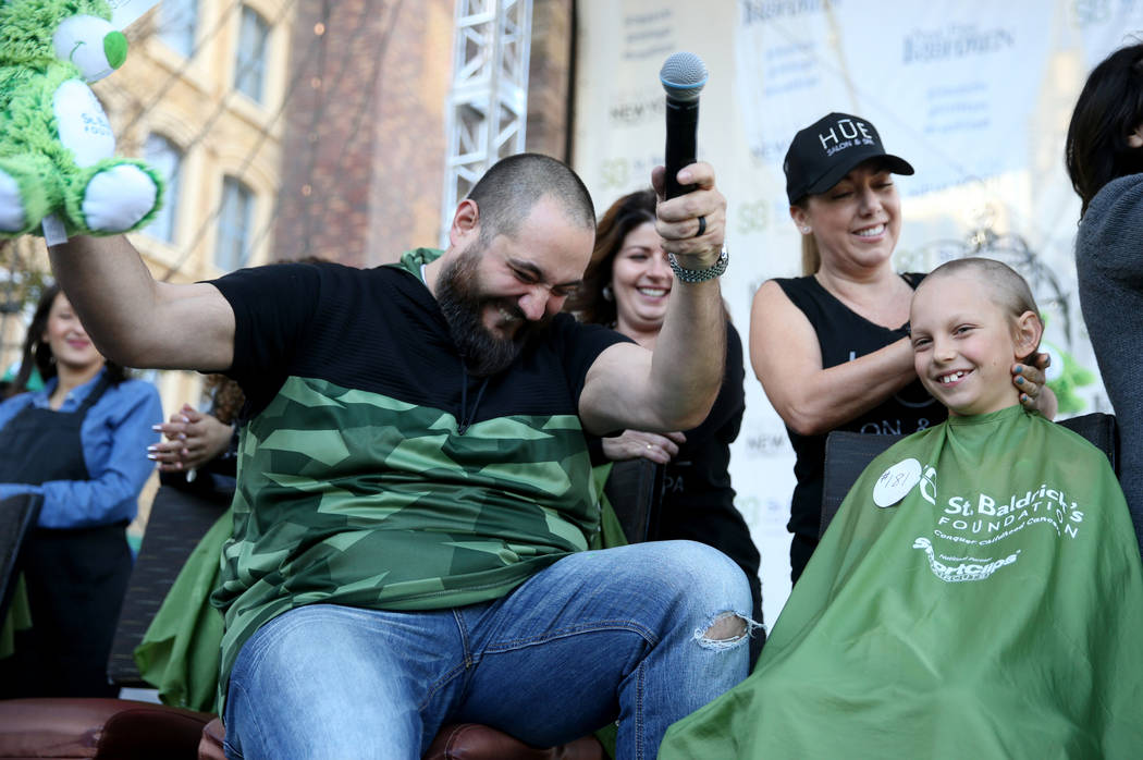 Dylan Foote, 8, of Las Vegas gets his head shaved by Jessica Buchmiller of Hue Salon in Las Vegas during St. Baldrick's Foundation shave-a-thon on the Brooklyn Bridge at New York-New York in Las V ...
