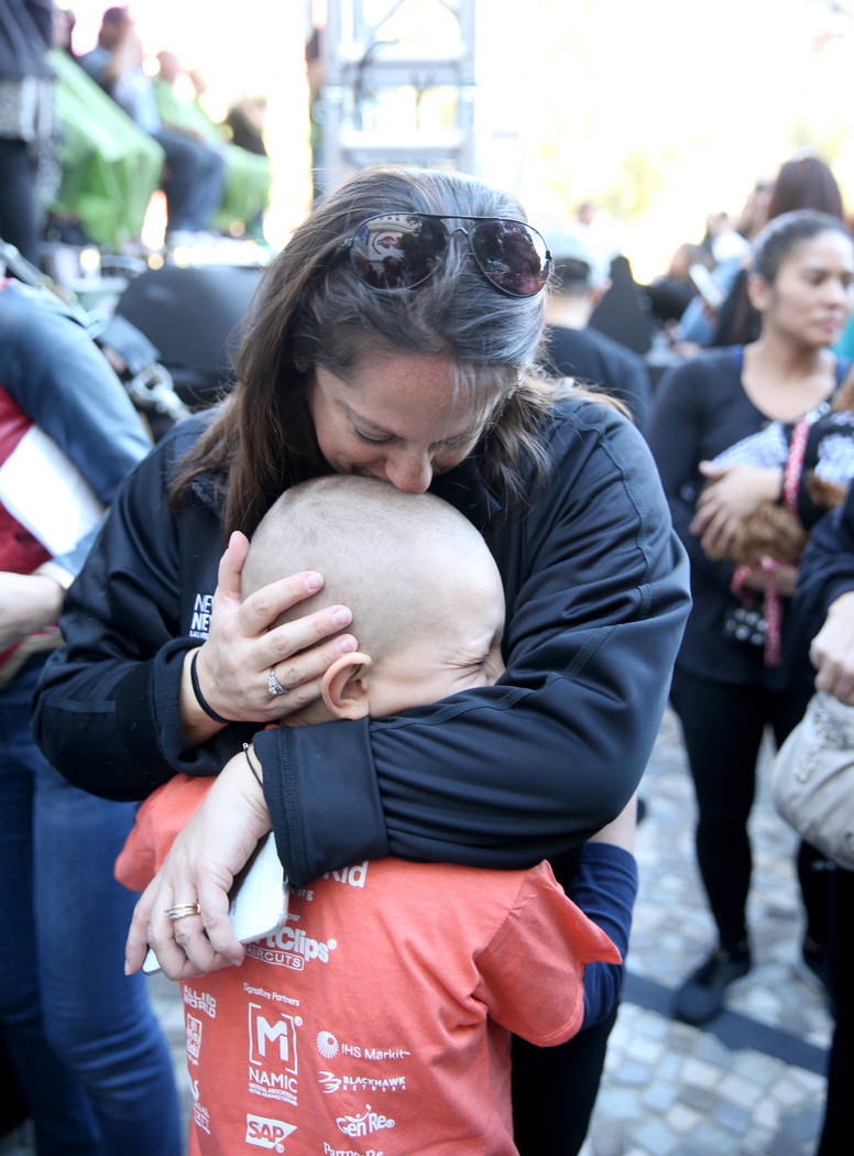 Dylan Foote, 8, of Las Vegas gets a hug from his mother Melanie after getting his head shaved during St. Baldrick's Foundation shave-a-thon on the Brooklyn Bridge at New York-New York in Las Vegas ...