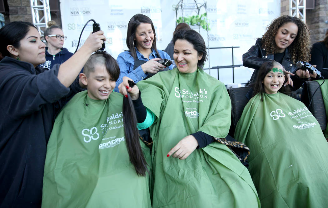 Katrin Ivanoff, of Las Vegas, center, with her children Ilian Ivanoff, 10, and daughter Katrin Ivanoff, 9, get their heads shaved by, from left, Genevie Valdivia, Kristina Rodriguez and Brianna Br ...