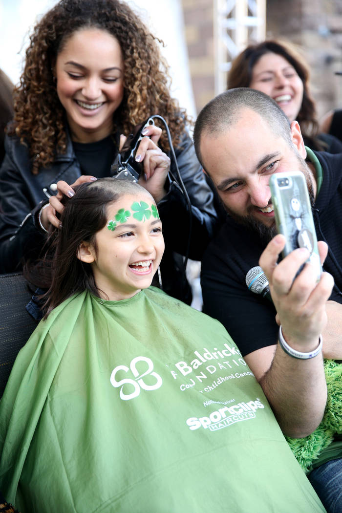 Katrin Ivanoff, 9, of Las Vegas, get her head shaved by Brianna Brown of Las Vegas, as Vegas Golden Knights host and radio personality Wayne 'Big D' Danielson shows her progress during St. Baldric ...