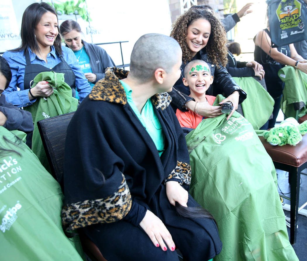 Katrin Ivanoff, 9, of Las Vegas, reacts to her mother, also Katrin Ivanoff, after getting their heads shaved during St. Baldrick's Foundation shave-a-thon on the Brooklyn Bridge at New York-New Yo ...