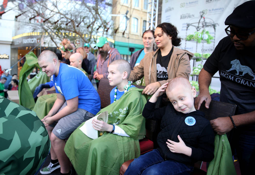 Preston Fitch, 4, of Las Vegas, reacts after getting his head shaved by MGM barber Anthony Banks during St. Baldrick's Foundation shave-a-thon on the Brooklyn Bridge at New York-New York in Las Ve ...