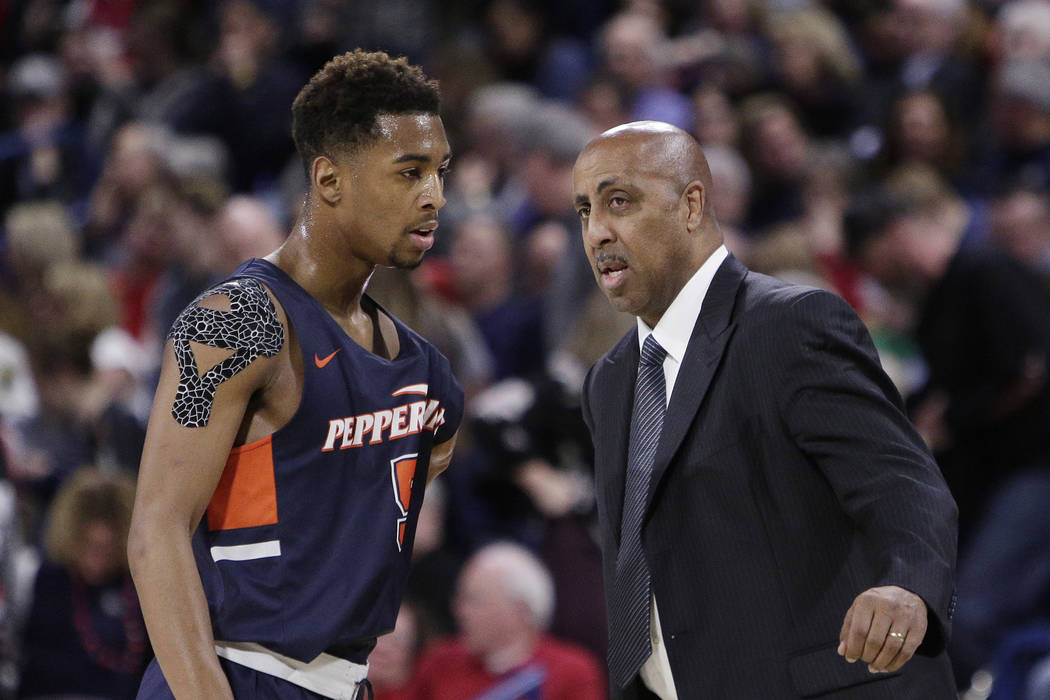 Pepperdine head coach Lorenzo Romar, right, speaks with guard Jade' Smith during the second half of an NCAA college basketball game against Gonzaga in Spokane, Wash., Thursday, Feb. 21, 2019. (AP ...
