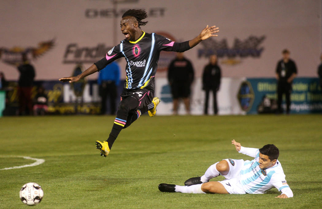 Las Vegas Lights FC midfielder Alex Nyarko Harlley (14) jumps over Austin Bold FC forward Julian Gaines (7) during the first half of a United Soccer League match at Cashman Field in Las Vegas, Sat ...