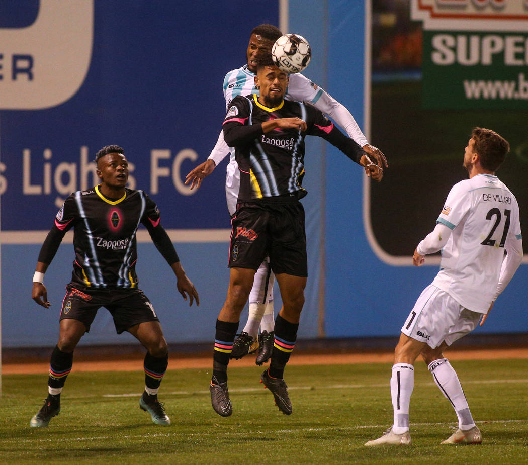 Las Vegas Lights FC defender Javan Torre (5) and Austin Bold FC defender Jermaine Taylor (4) both jump up to head the ball during the second half of a United Soccer League match at Cashman Field i ...
