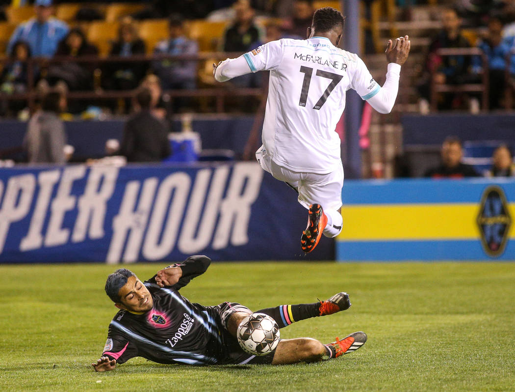 Las Vegas Lights FC midfielder Eric Gonzalez (28) slides to get the ball from Austin Bold FC defender Sean McFarlane (17) during the second half of a United Soccer League match at Cashman Field in ...