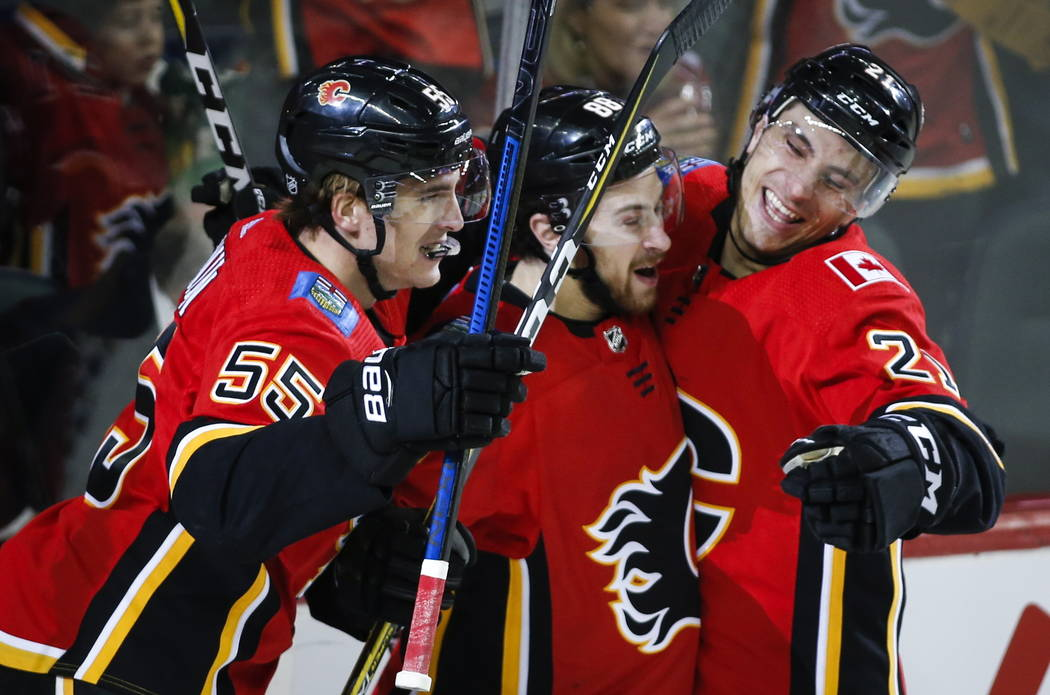 Calgary Flames' Andrew Mangiapane, centre, celebrates his goal with teammates Noah Hanifin, left, and Garnet Hathaway during first period NHL hockey action against the Vegas Golden Knights in Calg ...