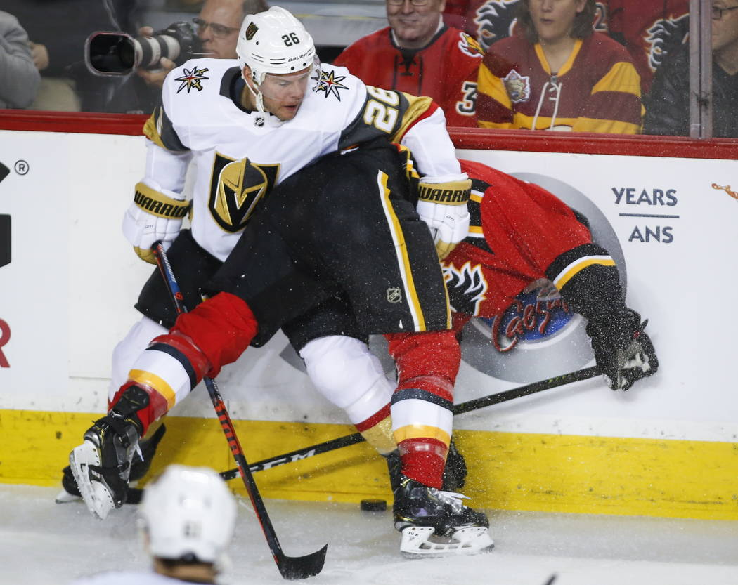 Vegas Golden Knights' Paul Stastny, left, takes Calgary Flames' T.J. Brodie into the boards during first period NHL hockey action in Calgary, Alberta, Sunday, March 10, 2019. (Jeff McIntosh/The Ca ...