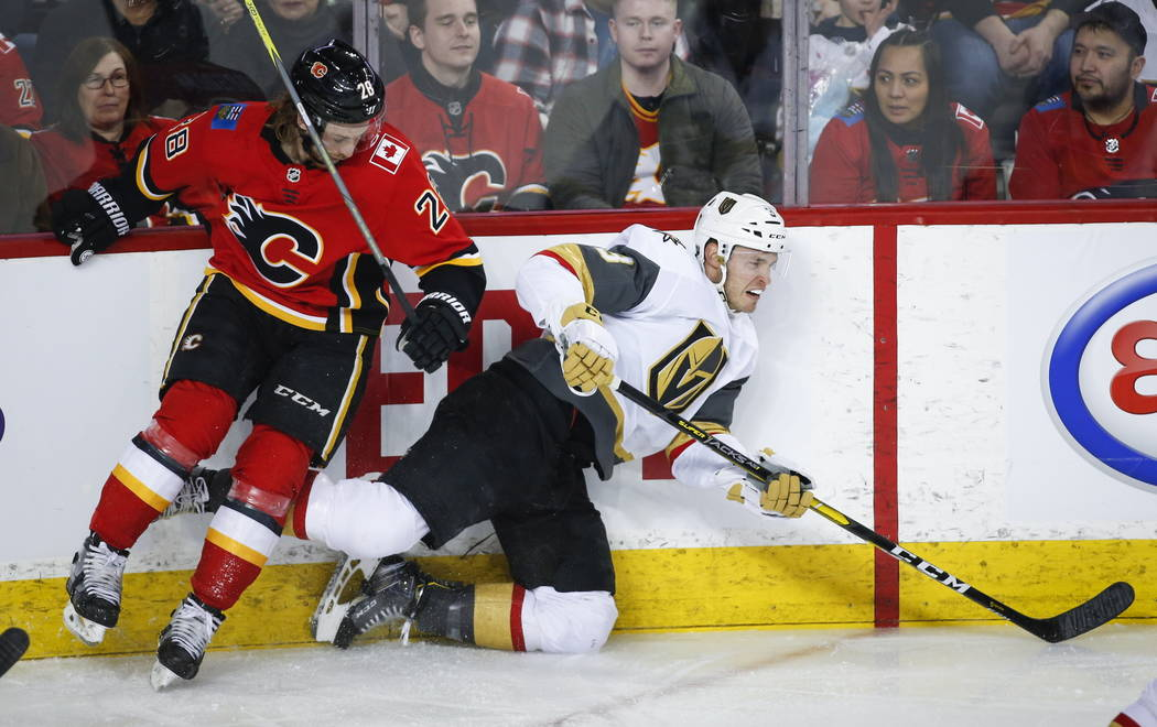 Vegas Golden Knights' Brayden McNabb, right, is checked by Calgary Flames' Elias Lindholm, of Sweden, during first period NHL hockey action in Calgary, Alberta, Sunday, March 10, 2019. (Jeff McInt ...