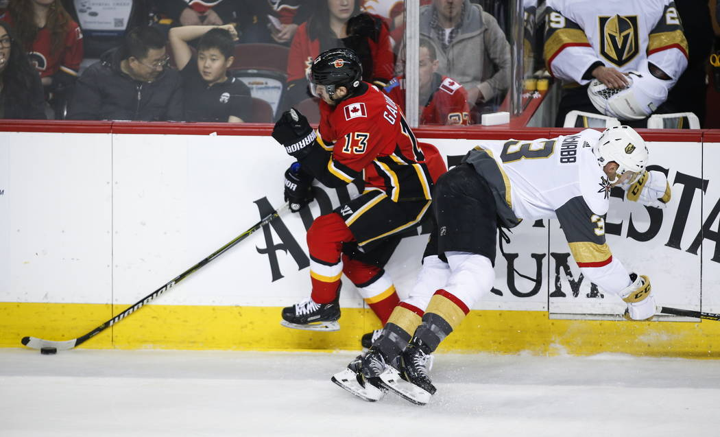 Vegas Golden Knights' Brayden McNabb, right, checks Callgary Flames' Johnny Gaudreau during first period NHL hockey action in Calgary, Alberta, Sunday, March 10, 2019. (Jeff McIntosh/The Canadian ...