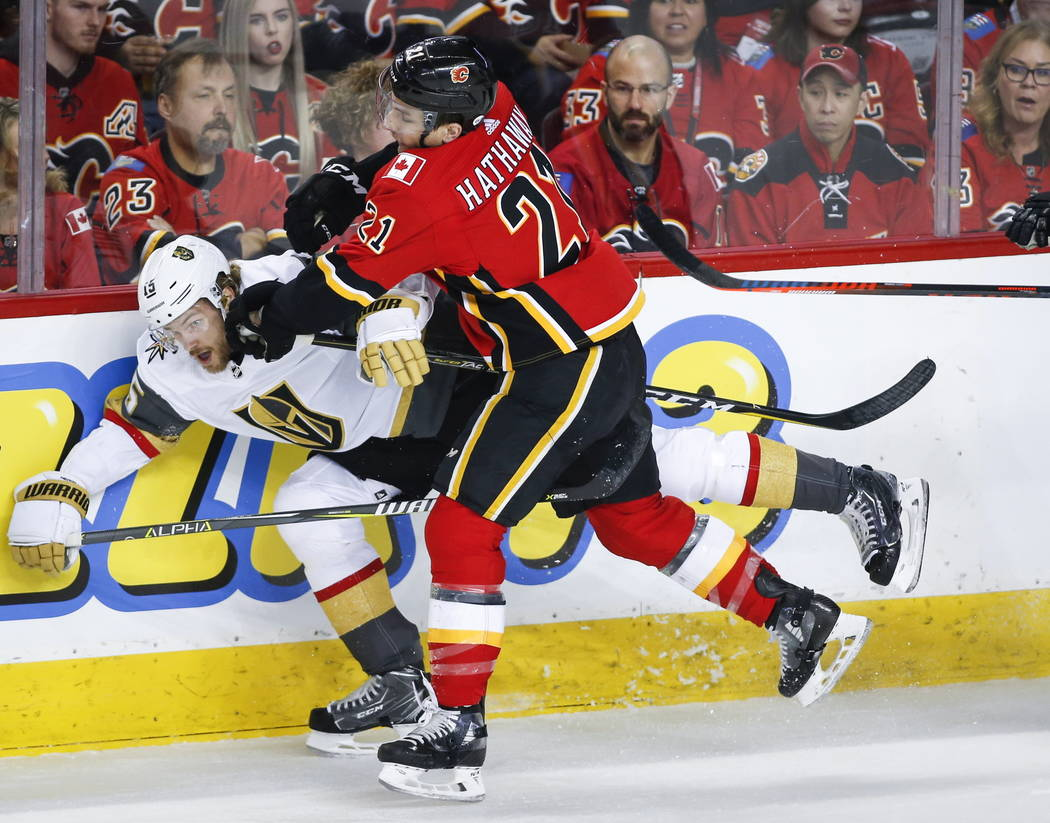 Vegas Golden Knights' Jon Merrill, left, is checked by Calgary Flames' Garnet Hathaway during first period NHL hockey action in Calgary, Alberta, Sunday, March 10, 2019. (Jeff McIntosh/The Canadia ...