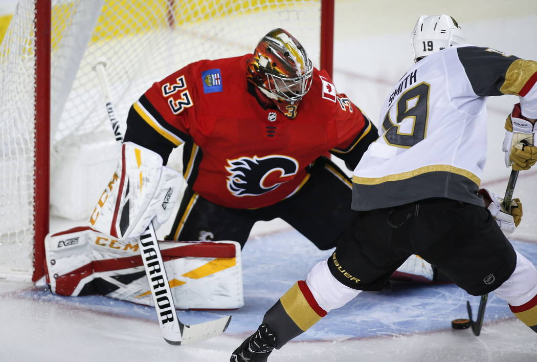 Vegas Golden Knights' Reilly Smith, right, scores on Calgary Flames goalie David Rittich, of the Czech Republic, during second period NHL hockey action in Calgary, Alberta, Sunday, March 10, 2019. ...