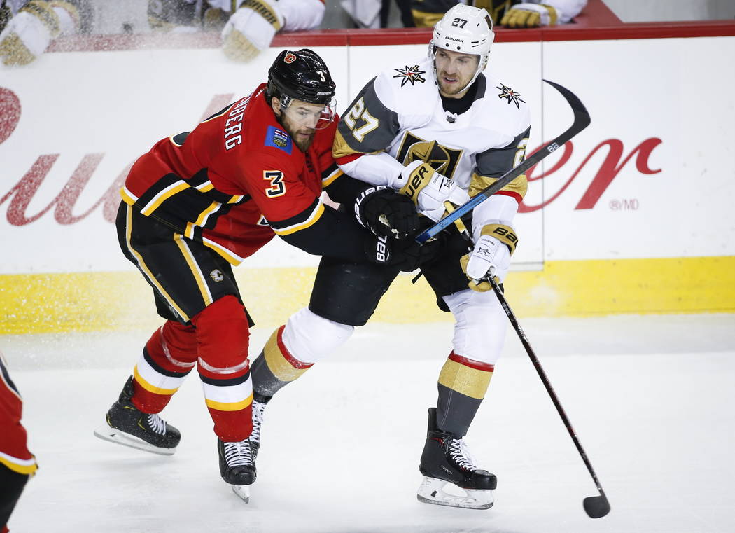 Vegas Golden Knights' Shea Theodore, right, is checked by Calgary Flames' Oscar Fantenberg, of Sweden, during second period NHL hockey action in Calgary, Sunday, March 10, 2019. (Jeff McIntosh/The ...