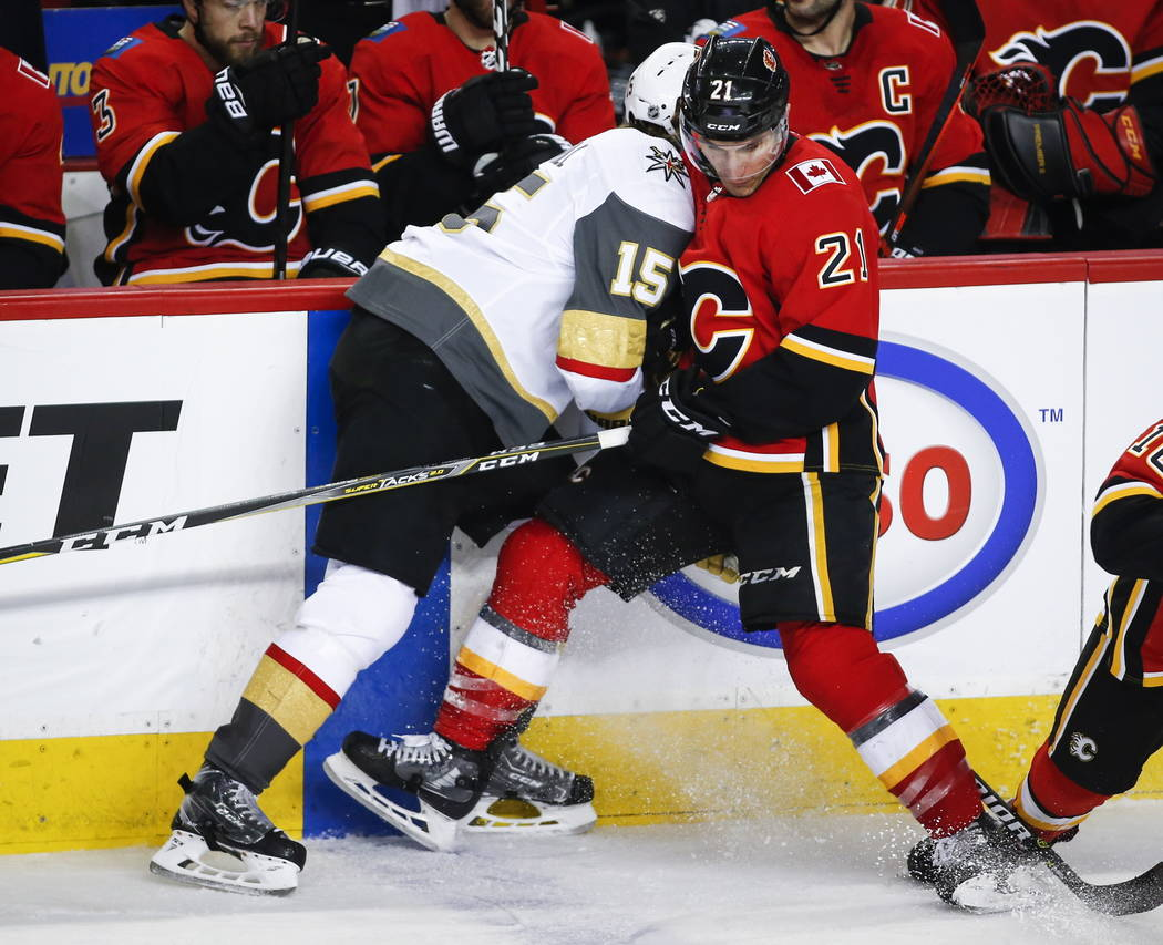 Vegas Golden Knights' Jon Merrill, left, checks Calgary Flames' Garnet Hathaway during the third period of an NHL hockey game in Calgary, Alberta, Sunday, March 10, 2019. The Flames won, 6-3. (Jef ...