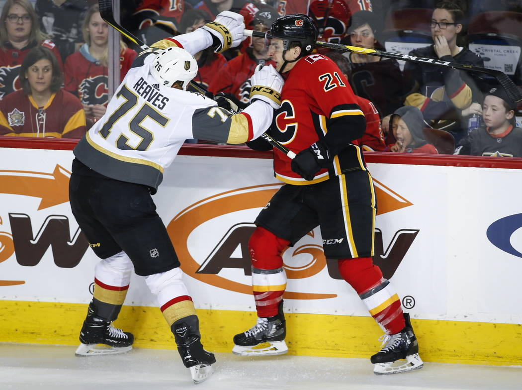 Vegas Golden Knights' Ryan Reaves, left, checks Calgary Flames' Garnet Hathaway during the third period of an NHL hockey game in Calgary, Alberta, Sunday, March 10, 2019. The Flames won, 6-3. (Jef ...