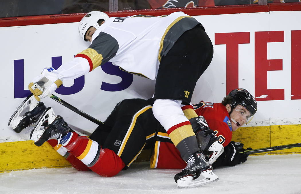 Vegas Golden Knights' Deryk Engelland, top, checks Calgary Flames' Matthew Tkachuk during the third period of an NHL hockey game in Calgary, Alberta, Sunday, March 10, 2019. The Flames won, 6-3. ( ...