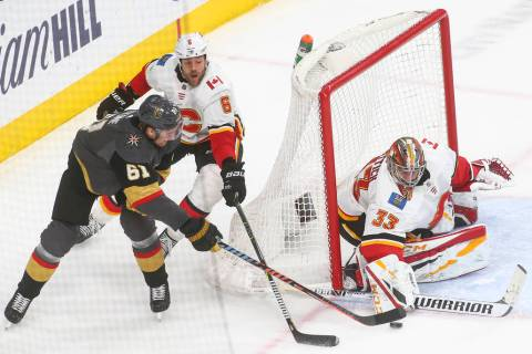 Golden Knights right wing Mark Stone (61) tries to get the puck in against Calgary Flames goaltender David Rittich (33) under pressure from defenseman Dalton Prout (6) during the third period of a ...
