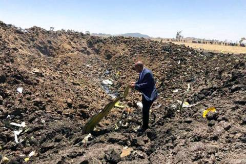 In this photo taken from the Ethiopian Airlines Facebook page, the CEO of Ethiopian Airlines, Tewolde Gebremariam, looks at the wreckage of the plane that crashed shortly after takeoff from Addis ...