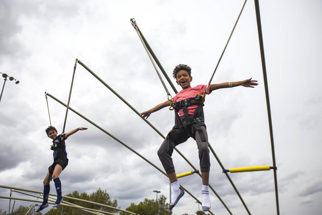 Kaj Freeborn, 9, left, and his brother Travis Williams, 10, on a jumping ride during Friendship Circle'sWalk4FriendshipLasVegas event at Las Vegas Sports Park, Sunday, March 10, ...