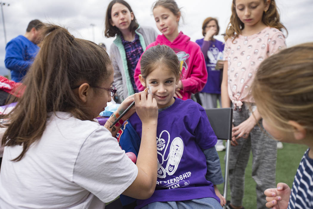 Julissa Toruno paints the face of Sheina Shomer, 5, during Friendship Circle'sWalk4FriendshipLasVegas eventat Las Vegas Sports Park, Sunday, March 10, 2019. Friendship Circ ...
