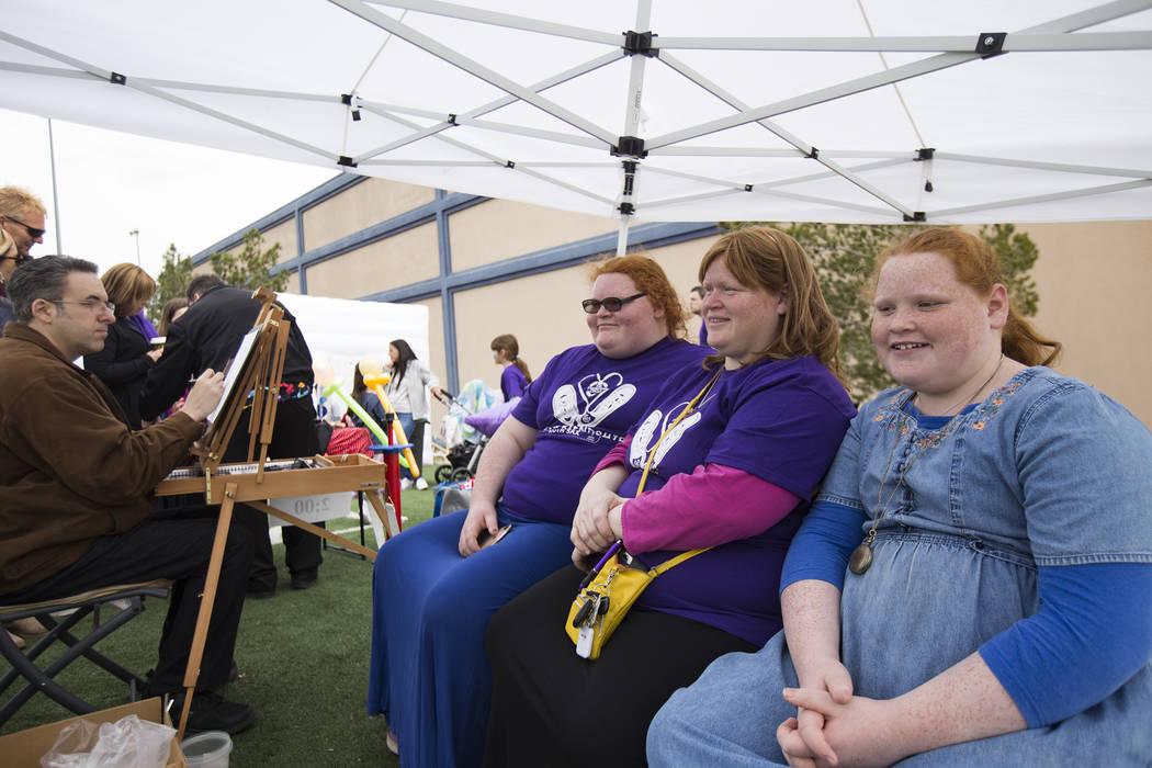 Shaina Kinn, from left, her mother Shoshana Kinn, and her sister Goldie Kinn, 13, have their caricature done at Friendship Circle'sWalk4FriendshipLasVegasevent at Las Vegas ...