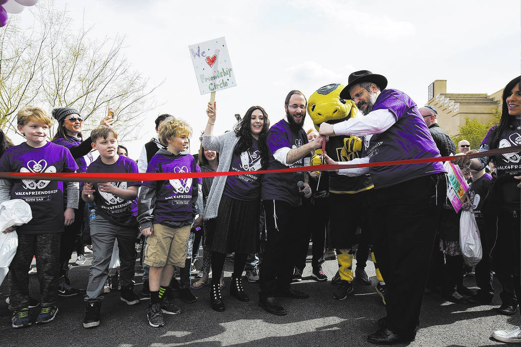 Nechama Harlig, holding a sign, from left, her husband Rabbi Levi Harlig, Chance the Golden Knights mascot, and Levi's father Rabbi Shea Harlig cut the ribbon to begin a walk from Bet Yossef Comm ...