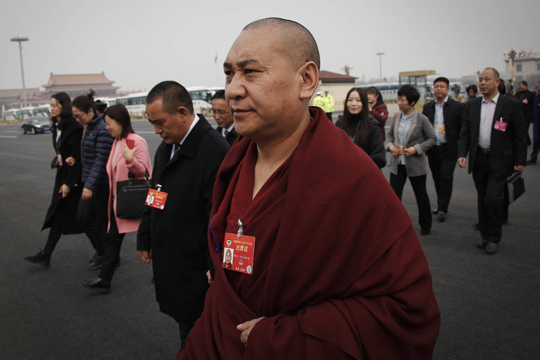 A Tibetan monk, a delegate to the Chinese People's Political Consultative Conference (CPPCC), arrives with other delegates to the Great Hall of the People to attend a plenary session of the CPPCC ...
