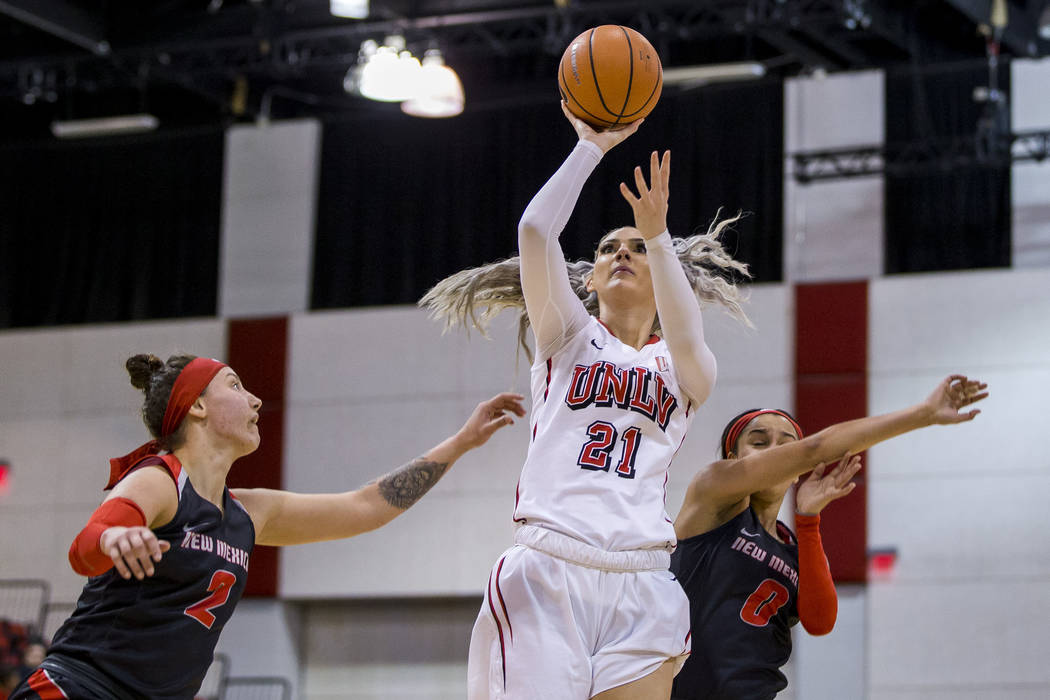 UNLV Rebels forward/center Katie Powell (21) goes up for a shot while defenders New Mexico Lobos guard Tesha Buck (2) and New Mexico Lobos guard Cherise Beynon (0) fall on her sides at Cox Pavilio ...