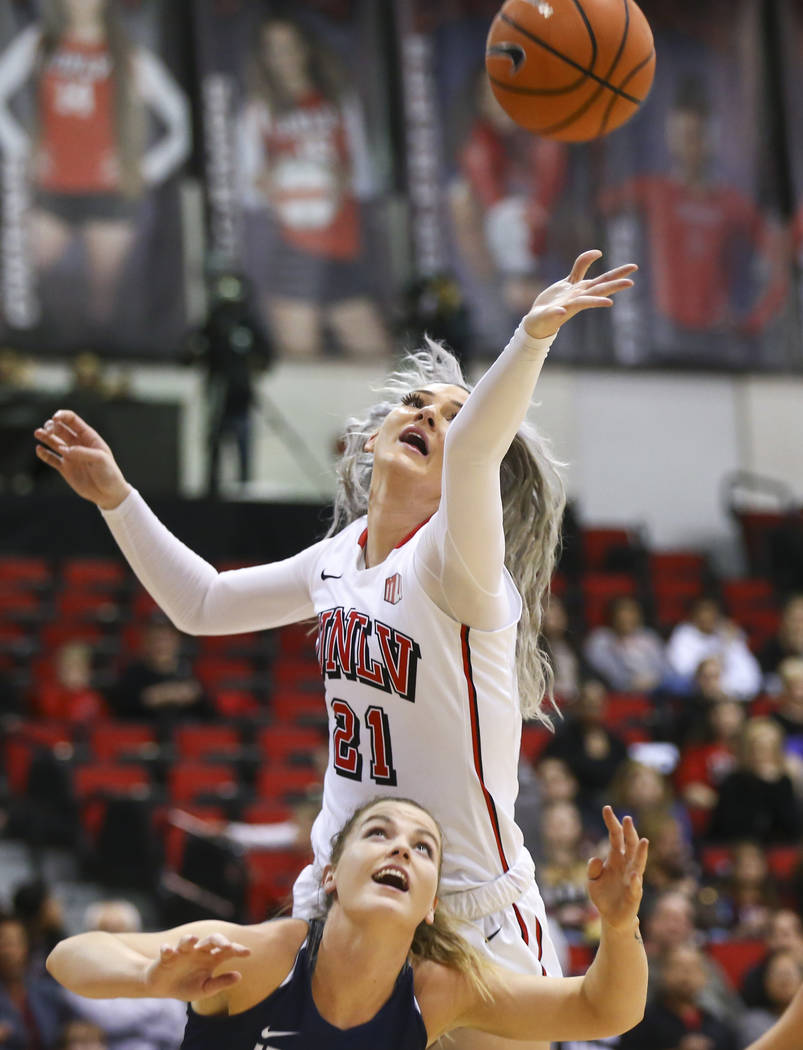 UNLV Lady Rebels forward/center Katie Powell (21) reaches for a rebound over Utah State Aggies guard Rachel Brewster (22) during the first half of a basketball game at the Cox Pavilion in Las Vega ...