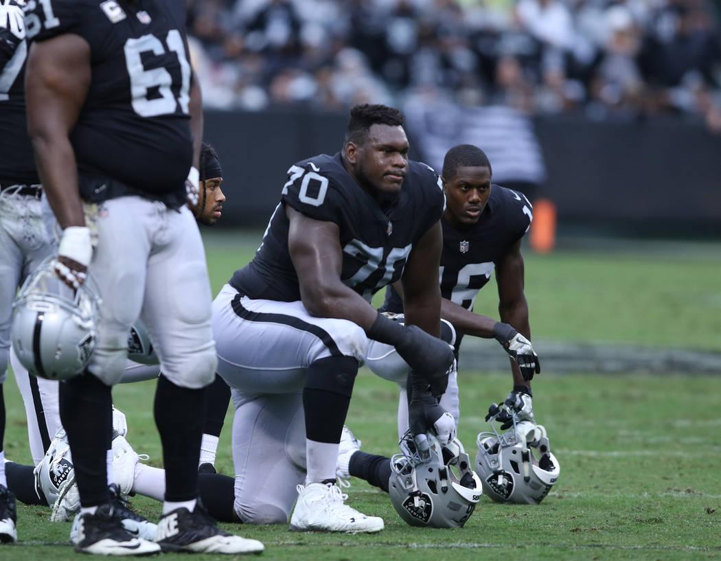 Oakland Raiders offensive guard Kelechi Osemele (70), wide receiver Johnny Holton (16) kneel. Heidi Fang Las Vegas Review-Journal @HeidiFang