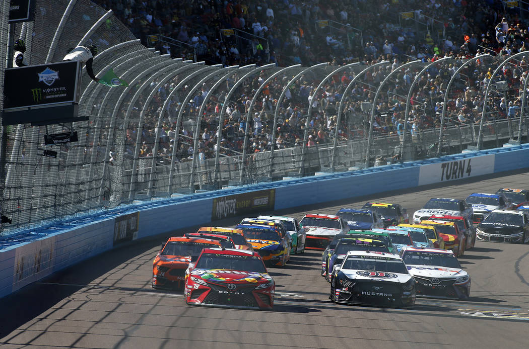 Kyle Busch (18) and Kevin Harvick (4) lead the field to the green flag on a restart during the NASCAR Cup Series auto race at ISM Raceway, Sunday, March 10, 2019, in Avondale, Ariz. (AP Photo/Ralp ...
